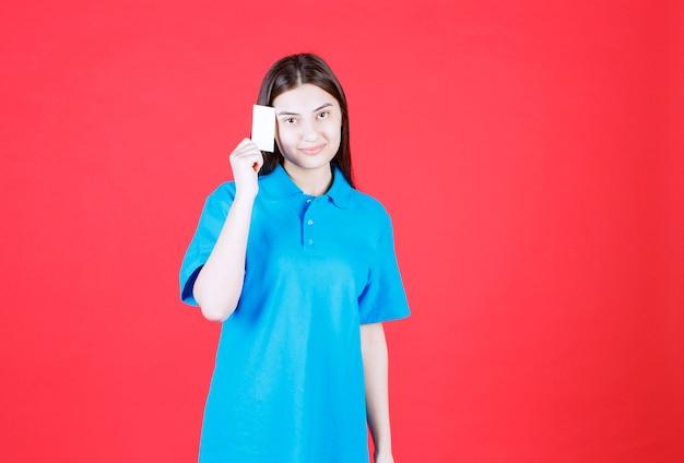 Ragazza in camicia blu che presenta il suo biglietto da visita e sembra premurosa.