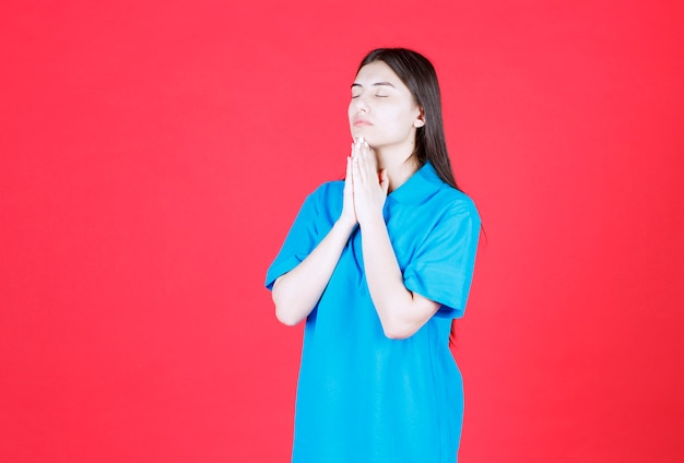 Girl in blue shirt standing on red background, uniting hands and praying