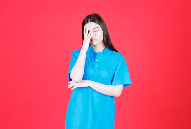 Girl in blue shirt standing on red wall and looks tired and sleepy