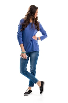 Girl in blue sweater. woman in jeans holds phone. sports watch and new smartphone. fashionable spring wear.