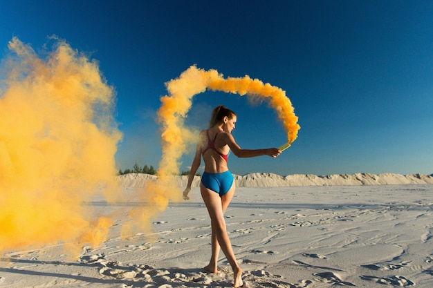 Girl in blue swim-suit dances with orange smoke on white beach