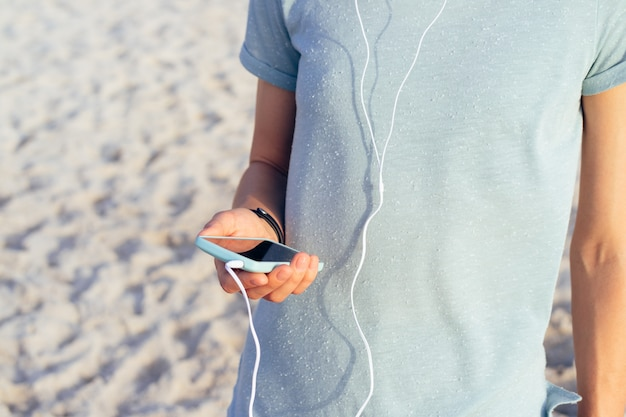 Girl in a blue t-shirt holding a mobile phone in hand and listening to music with headphones on the beach