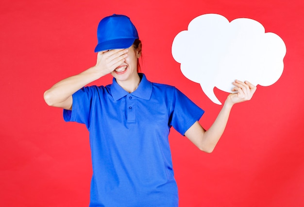Ragazza in uniforme blu e berretto che tiene in mano una lavagna a forma di nuvola e sembra stanca e ha mal di testa.