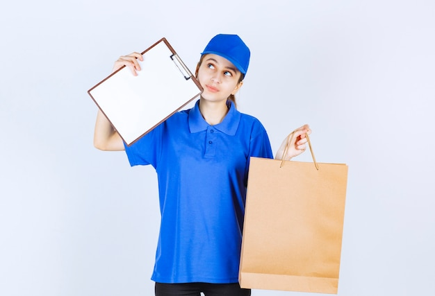 Girl in blue uniform holding a cardboard shopping bag and a customer list.