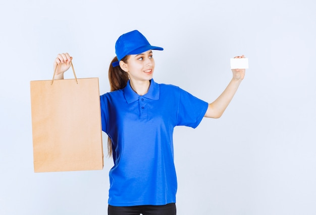 Girl in blue uniform holding a cardboard shopping bag and presenting her business card.