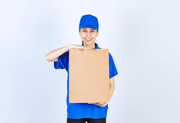 Girl in blue uniform holding a cardboard shopping bag.