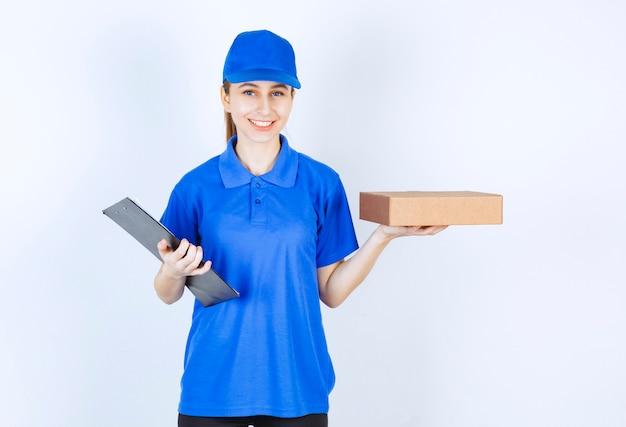 Girl in blue uniform holding a cardboard takeaway box and a customer list.
