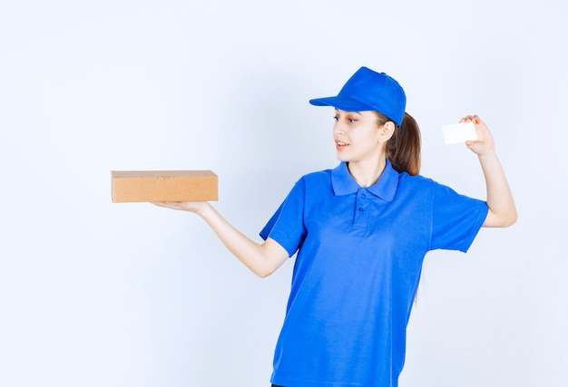 Girl in blue uniform holding a cardboard takeaway box and presenting her business card.