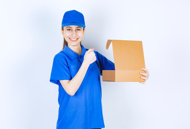 Girl in blue uniform holding an open cardboard takeaway box and showing her fist.