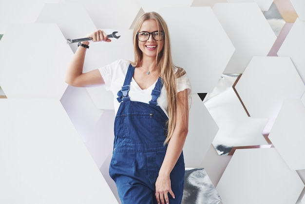 Girl in blue uniform stands against abstract wall with white pieces of surface in the shape of hexagon in the auto saloon