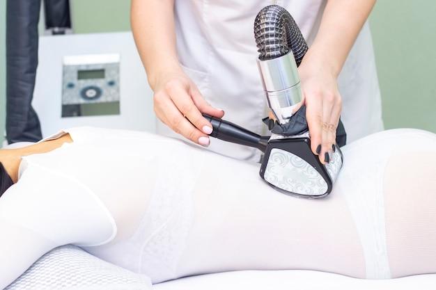 Массаж тела девушки в спа. девушке делают аппаратный массаж, на ней специальный комбинезон для массажа. кавитация, целлюлит, потеря жира.