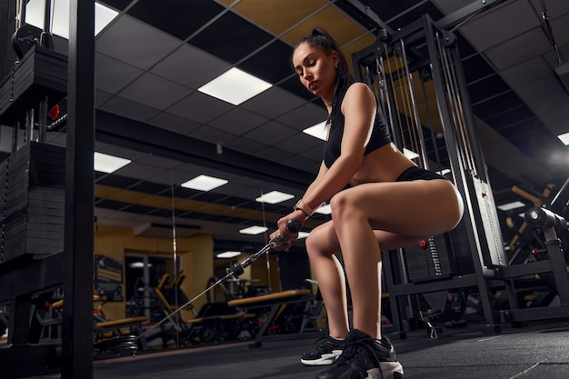 A girl bodybuilder trains in the gym