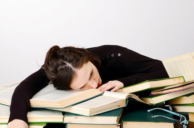 Девушка книги экзамен черный свитер трудности учит за столом усталый радуется эмоции