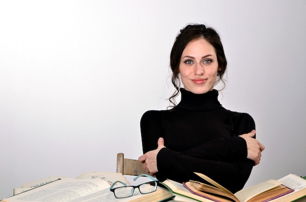 Girl books exam black sweater difficulties teaches at the table tired rejoices emotions