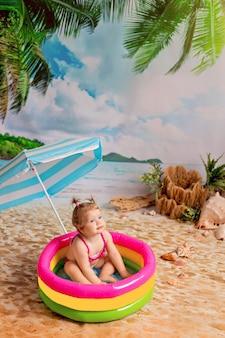 女の子男の子は海沿いの砂浜のビーチパラソルの下の膨脹可能なプールで入浴します。