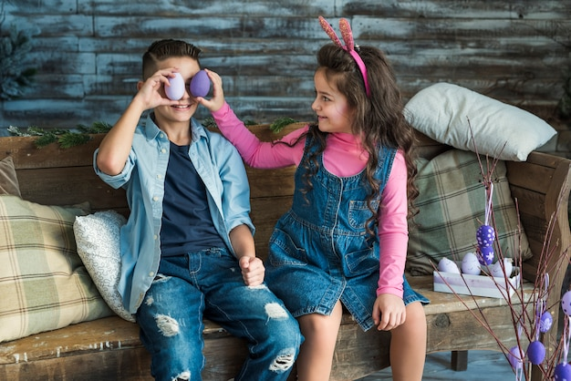 Girl and boy holding easter eggs at eyes