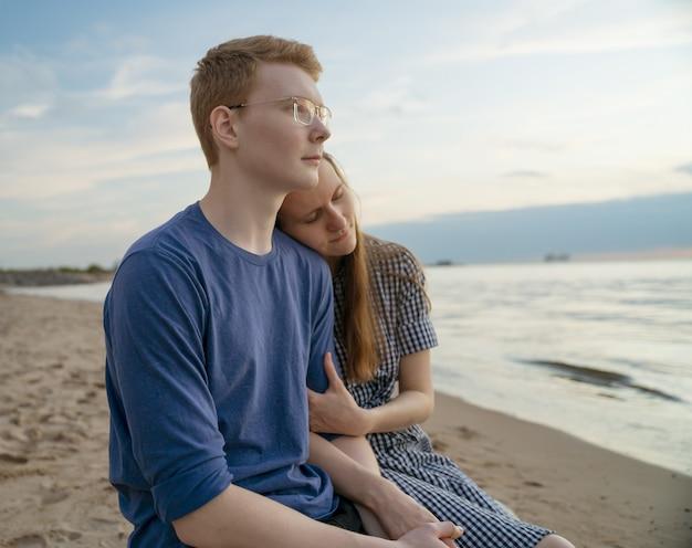 Girl and boy sitting, girlfriend hold boyfriend hand