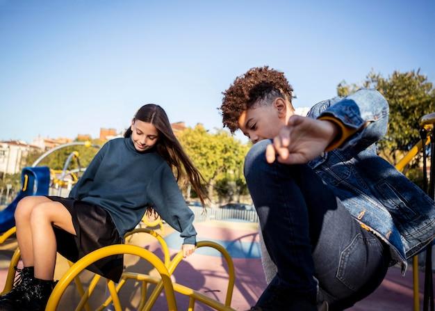 Ragazza e ragazzo che trascorrono del tempo insieme nel parco all'esterno