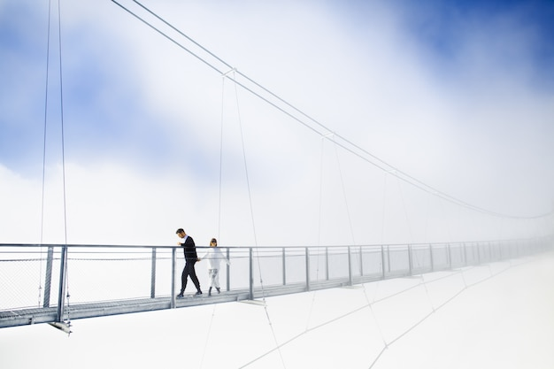 Girl and boy walking on bridge in clouds