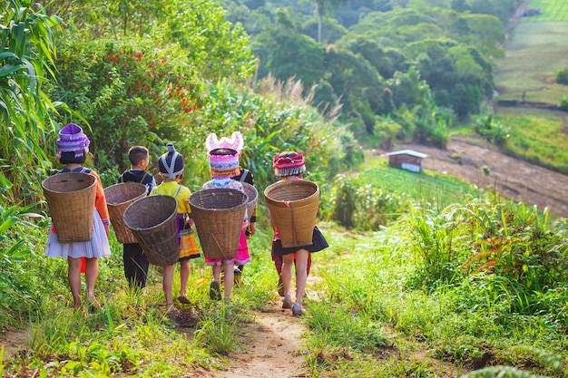 The girl and boy wearing a hmong dress carry bamboo basket on her back on the path to thei