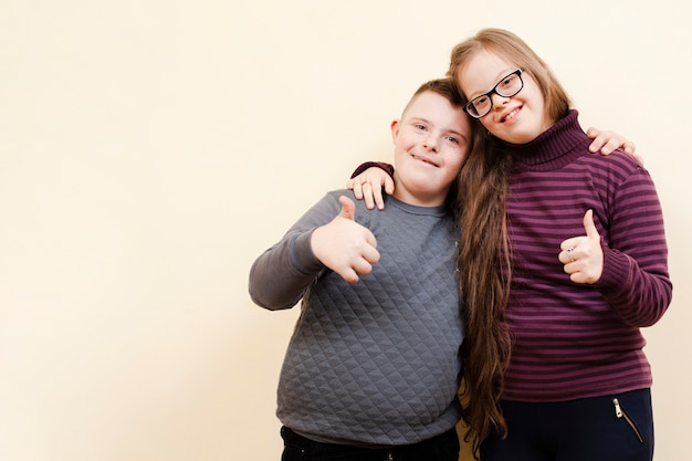 Girl and boy with down syndrome posing and giving thumbs up