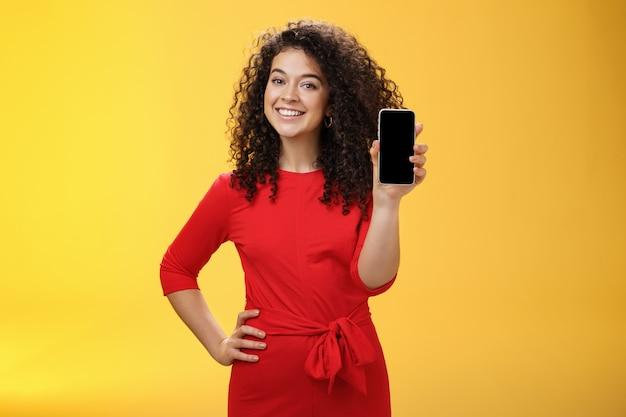 Девушка хвастается новым телефоном, купленным на рождество, чувствуя себя счастливой, держа в руке мобильное устройство ...