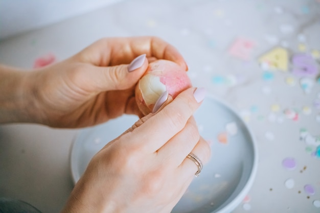 Girl breaks golden easter eggs on marble background, confetti, sparkles, ribbons.