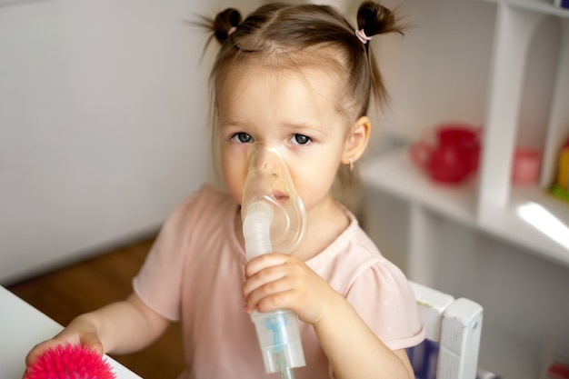 A girl breathes into an inhalation mask