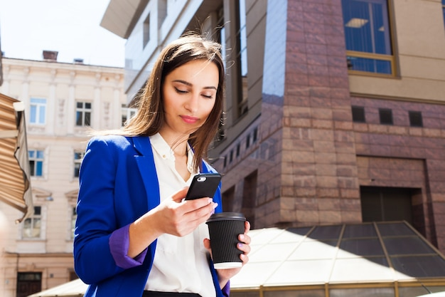 Ragazza in giacca blu brillante si trova con smartphone e caffè sulla strada