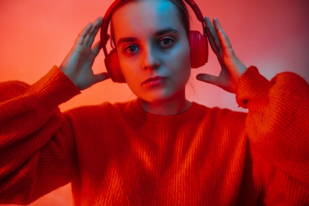 A girl in bright colored lighting listens to music with headphones