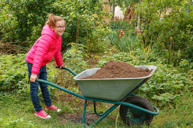 Girl in a bright pink jacket is trying to move a heavy wheelbarrow with sand.