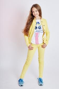 소녀 밝은 여름은 아름다운 옷을 보입니다. 노란색 데님 정장. 밝은 배경에 웃 고 포즈를 취하는 소녀.