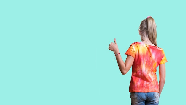 A girl in a bright tie dye t-shirt on a light turquoise surface