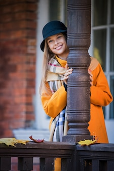 Girl in a bright yellow coat on the veranda of the house