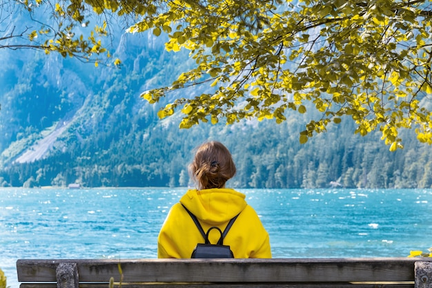 A girl in a bright yellow hoodie sits on a bench by the lake in the mountains.