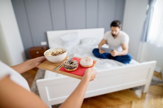 Девушка приносит тарелку с хлопьями и пончиками молодому человеку, сидящему на кровати и проверяющему планшет.
