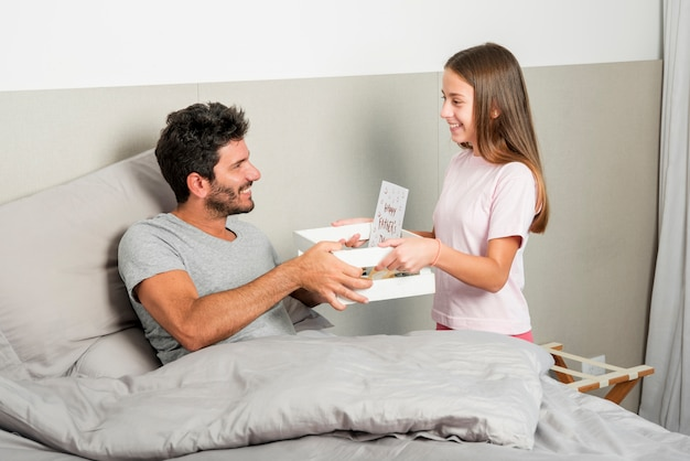 女の子は父親の日に朝食をもたらす