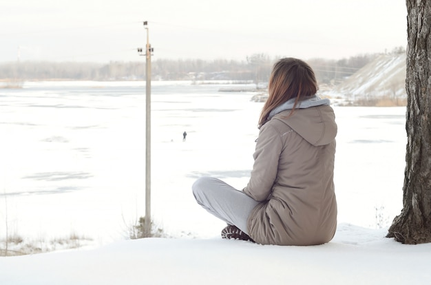 Girl in a brown coat staring into the horizon line between the sky and the frozen lake in winter
