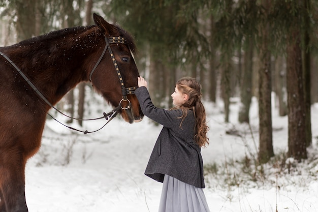 Girl and brown horse in winter in nature