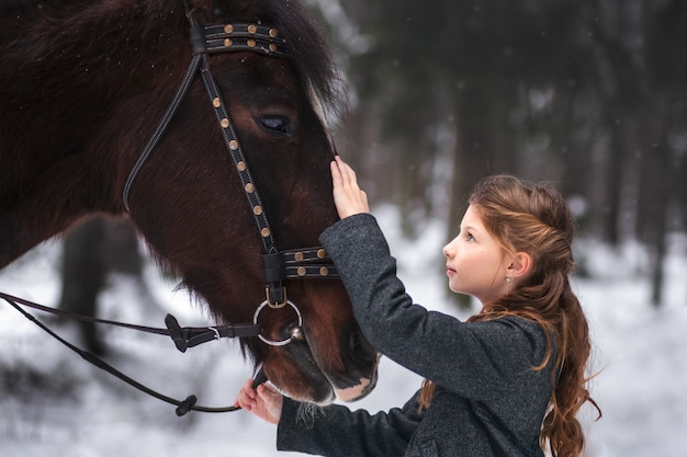 Girl and brown horse in winter