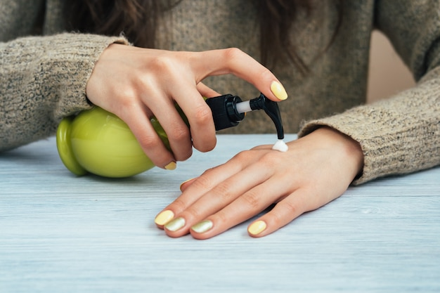 Girl in brown sweater with yellow manicure applying hand cream, close-up