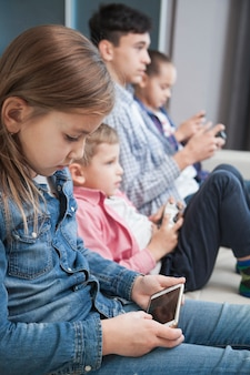 Girl browsing smartphone near brothers and sister