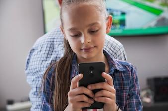 Girl browsing smartphone near teenager
