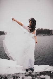 Девушка брюнетка невеста в свадебном платье зимой моя в снегу