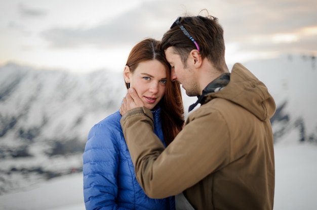 Girl brunette looking into the frame while her hugging guy against the snow-covered mountains