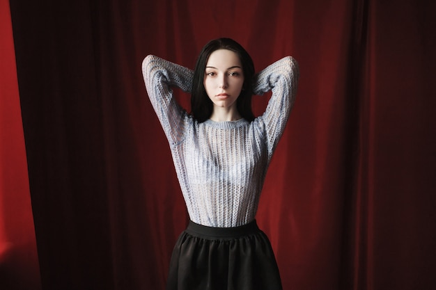 Girl brunette with long straight black hair with a natural make-up pose on red. a woman in a blue knitted sweater.
