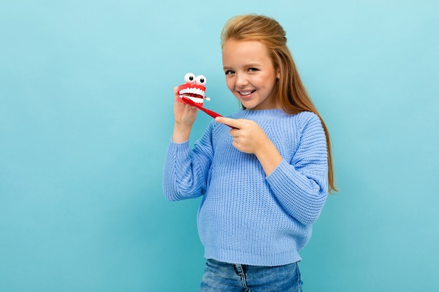Girl brushes teeth on a blue studio background.