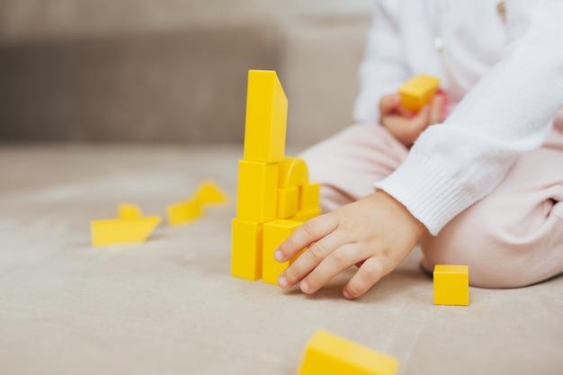 黄色のおもちゃのビルディングブロックから建物を構築する女の子