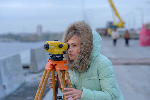 The girl the builder in warm clothes looks in a theodolite.