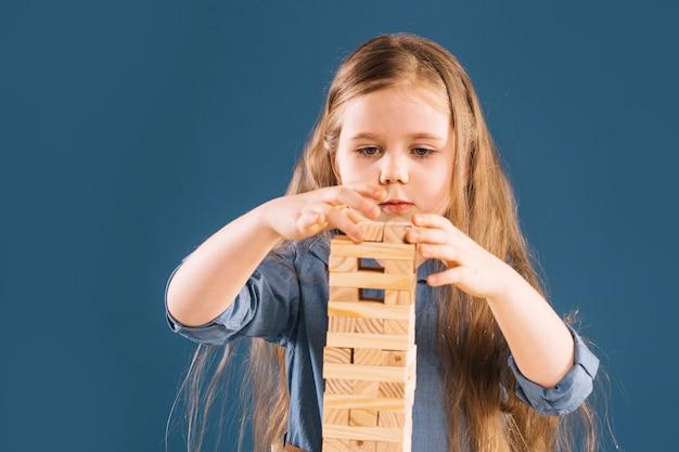 Girl building jenga tower